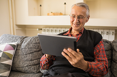 Image of older gentleman in a Care Home Assisted Living reading a blog on a tablet.